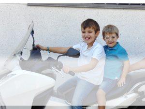 Foto representativa de dos niños sonrientes subidos a una moto parada, Asociación VIVO, ocio inclusivo y tiempo libre con y sin discapacidad, en Madrid